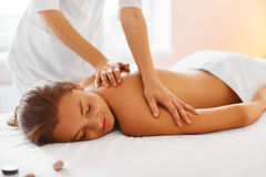 Spa treatment. Woman enjoying massage in spa centre. Stock Images