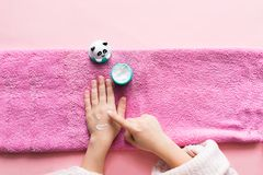 Spa treatments for hand skin and nails for children. Young girl`s hands lie on pink soft towel smeared with white cream. royalty free stock images