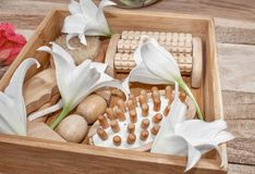 Spa treatments and massage products. Bathroom amenities, top view on a wooden table, decorated with flowers. Gift box for a woman. stock photo