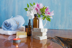 Spa treatments on wooden table blue background. Spa and wellness setting with natural soap and flowers, candles, massage oils and soft blue towel Stock Image