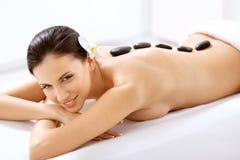 Spa Tretment. Kvinna som får stenmassage Arkivbild