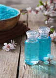 Spa. Two small  bottls with shower gel,  mineral bath salts, towels and spring flowers on the wooden table. Spa concept Stock Photography