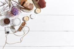 Spa uppsättning med det salta havet, nödvändig olja, tvål och handduken som dekoreras med den torra blomman på vit träbakgrund Fotografering för Bildbyråer
