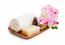 Spa uppsättning med organisk tvål, nödvändig olja, mjuk handduk och orkidé f arkivfoto