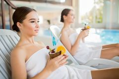 Spa vacation. Pretty girl wrapped in white towel and her friend enjoying spa vacation by swimming-pool Royalty Free Stock Images