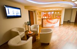SPA waiting room interior with leather chairs. A small SPA waiting room with comfortable armchairs and reception desk stock photo