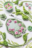 Spa or Wellness background. Bowl in shape of tropical leaf with flowers and water on white background with green leaves and calla. Flowers, top view. Beauty royalty free stock image
