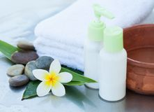Spa or wellness background with white towels, tropical leaves, flowers, body and face care tools and accessories on white. Background royalty free stock images