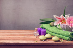 Spa and wellness concept with fresh towel, candles and flowers on wooden table Stock Image