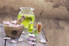Spa and wellness concept: preparation of essential oil with pink roses, bottle of tincture and mortar on a wooden board royalty free stock images