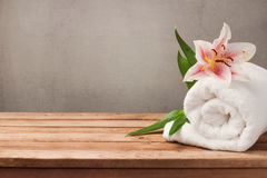 Spa and wellness concept with white towel and flower on wooden table over rustic grey background Stock Photo
