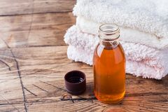 Spa and Wellness concept on wooden background. Terry towel and cosmetic oil for massage. Spa and Wellness concept on wooden background. Terry towel and cosmetic stock image