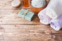 Spa and Wellness concept on wooden background. Terry towel and cosmetic oil for massage. Spa and Wellness concept on wooden background. Terry towel and cosmetic stock images