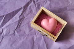 Spa and wellness concept: wooden box with pink sea salt and heart shape soap with word `love` on it Royalty Free Stock Images