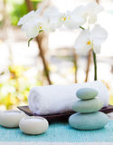 Spa and wellness massage setting Still life with candle, towel and stones Outdoor summer background. With fresh white orchid Copy space Royalty Free Stock Images