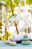 Spa and wellness massage setting Still life with candle, towel and stones Outdoor summer background. With fresh white orchid Copy space Royalty Free Stock Photos