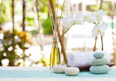 Spa and wellness massage setting Still life with candle, towel and stones Outdoor summer background. With fresh white orchid Copy space Royalty Free Stock Photo
