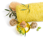Spa or wellness olive setting. Top view of aroma olive oil, towel and scrub brush isolated on a white background Royalty Free Stock Photography