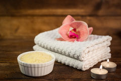 Spa or wellness set. Yellow sea salt in white bowl, towels, cand Royalty Free Stock Photos