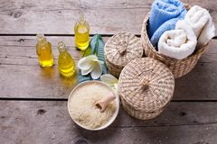 Spa or wellness setting in blue, yellow and white colors. Bottles wih essential aroma oil, towels, sea salt  on  aged wooden background. Selective focus Stock Image