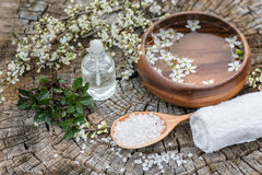 Spa and wellness setting with sea salt, oil essence, flowers and Stock Image