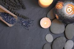 Spa and wellness still life composition with candles and pebble stones. Spa and wellness still life composition with candles, pebble stones and bath salt on dark stock images