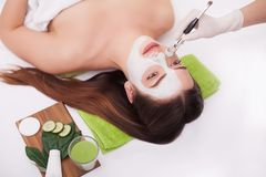 Spa Woman applying Facial cleansing Mask. Beauty Treatments. Clay mask Royalty Free Stock Images