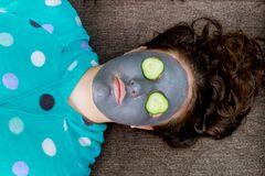 Spa Woman applying Facial cleansing Mask. Beauty Treatments. Mask on the face of a young girl royalty free stock image