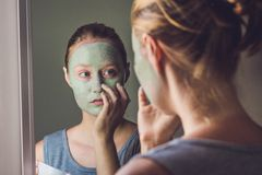 Spa Woman applying Facial green clay Mask. Beauty Treatments. Cl Stock Images