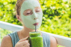 Spa Woman applying Facial green clay Mask. Beauty Treatments. Fresh green smoothie with banana and spinach with heart of sesame se Stock Image