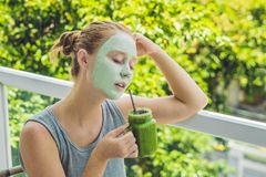 Spa Woman applying Facial green clay Mask. Beauty Treatments. Fresh green smoothie with banana and spinach with heart of sesame se Stock Photos