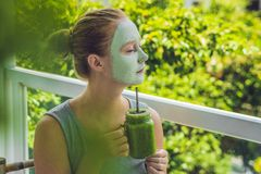 Spa Woman applying Facial green clay Mask. Beauty Treatments. Fresh green smoothie with banana and spinach with heart of sesame se Royalty Free Stock Images