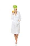 Spa woman in bathrobe holding orange. Stock Photography