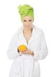 Spa woman in bathrobe holding orange. Stock Image