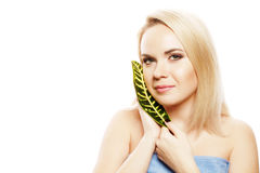 Spa woman. Beautiful blonde girl after bath. Portrait of a spa woman. Beautiful blonde girl after bath touching her face with a leaf of tropical plant. Perfect Stock Photography