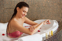 Spa Woman. Beautiful Woman in Bath Cares About Her Hands. Body c Stock Photos