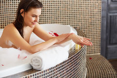 Spa Woman. Beautiful Woman in Bath Cares About Her Hands. Body c Royalty Free Stock Photo