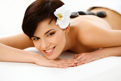 Spa Woman. Beautiful Woman Getting Hot Stones Massage. In Spa Salon. High quality image stock photo