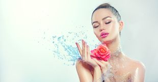 Spa woman. Beauty smiling girl with splashes of water and rose in her hands Royalty Free Stock Image