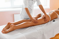Spa woman. Body care. Legs massage in spa salon. Body Care. Close-up Of Beautiful Long Tanned Woman Legs Receiving Massage In Spa Salon. Skin Care, Wellbeing Royalty Free Stock Photo