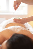 Spa Woman. Brunette Getting a Salt Scrub Beauty Treatment in the Royalty Free Stock Photography