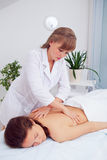 Spa woman. Female enjoying relaxing back massage in cosmetology spa centre. Body care, skin care, wellness, wellbeing Royalty Free Stock Photos