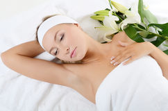 Spa Woman lays with a white lily Royalty Free Stock Images