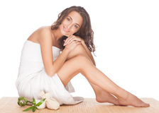 Spa woman. Portrait of beautiful young spa woman with healthy skin sitting and hugging her legs. Isolated on white background Stock Images