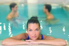 Spa woman portrait relaxed in pool water. Men in background Royalty Free Stock Images