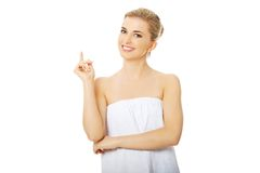 Spa woman wrapped in towel pointing up. Royalty Free Stock Photography