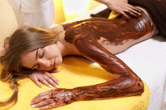 Spa Woman. Young Woman Gets Chocolate Body Mask at Beauty Salon Stock Photography