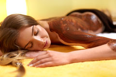 Spa Woman. Young Woman Gets Chocolate Body Mask at Beauty Salon Royalty Free Stock Photo