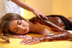 Spa Woman. Young Woman Gets Chocolate Body Mask at Beauty Salon Royalty Free Stock Images