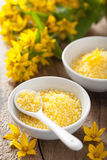 Spa with yellow herbal bath pearls and flowers Stock Photos